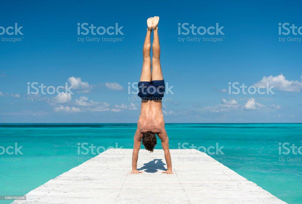 Männlicher Athlet Tourist, Handstand, Pier in Cancun, Mexiko – Foto