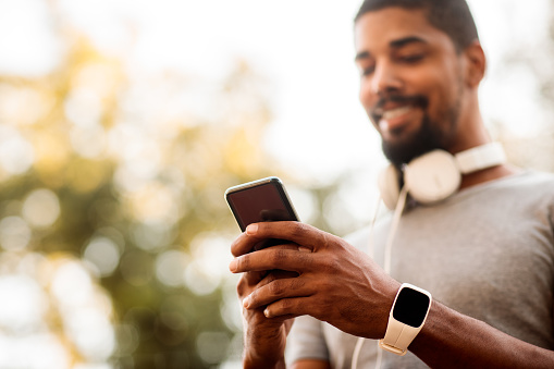African-American male with smart watch and headphones texting messages on mobile phone during running session.