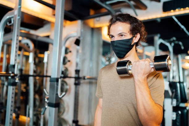 Male athlete wearing protective face mask and training with dumbbell in gym stock photo