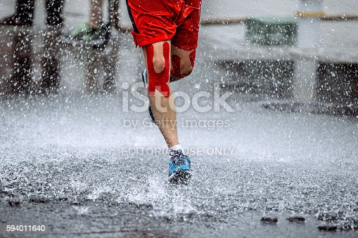 Ekaterinburg, Russia - August 7, 2016: male athlete with tape on his knees running through a puddle of water, splashes and drops around feet during Marathon Europe-Asia