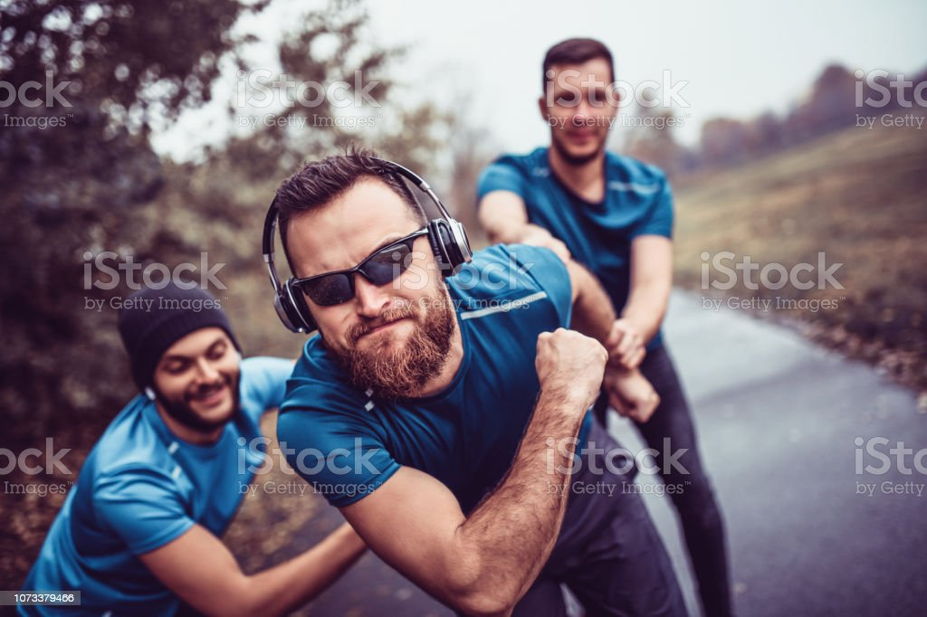 Male Athletes Making Funny Poses While Running In Public