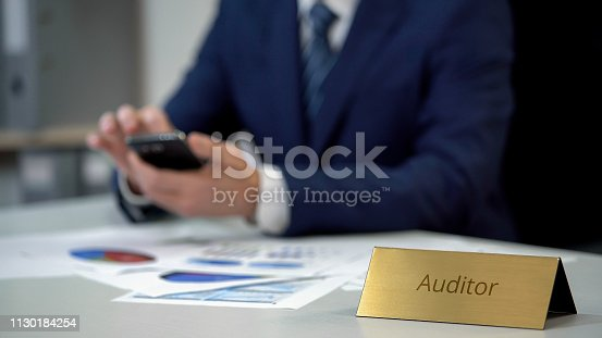 1130184417 istock photo Male auditor with smartphone working in office, checking financial report data 1130184254