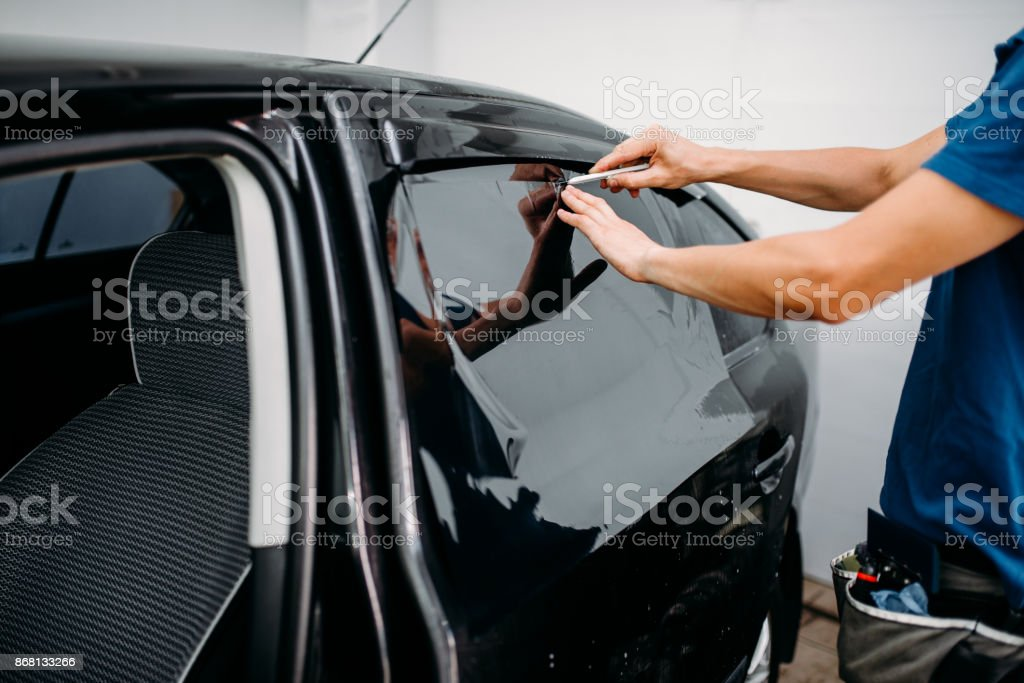 Male auto wrapper with blade, car tinting film stock photo