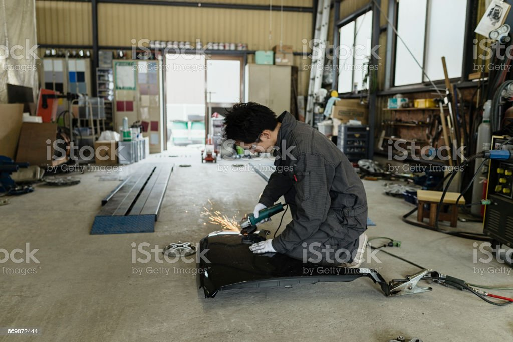 Male autobody technician fixing a damaged car in an auto repair shop stock photo