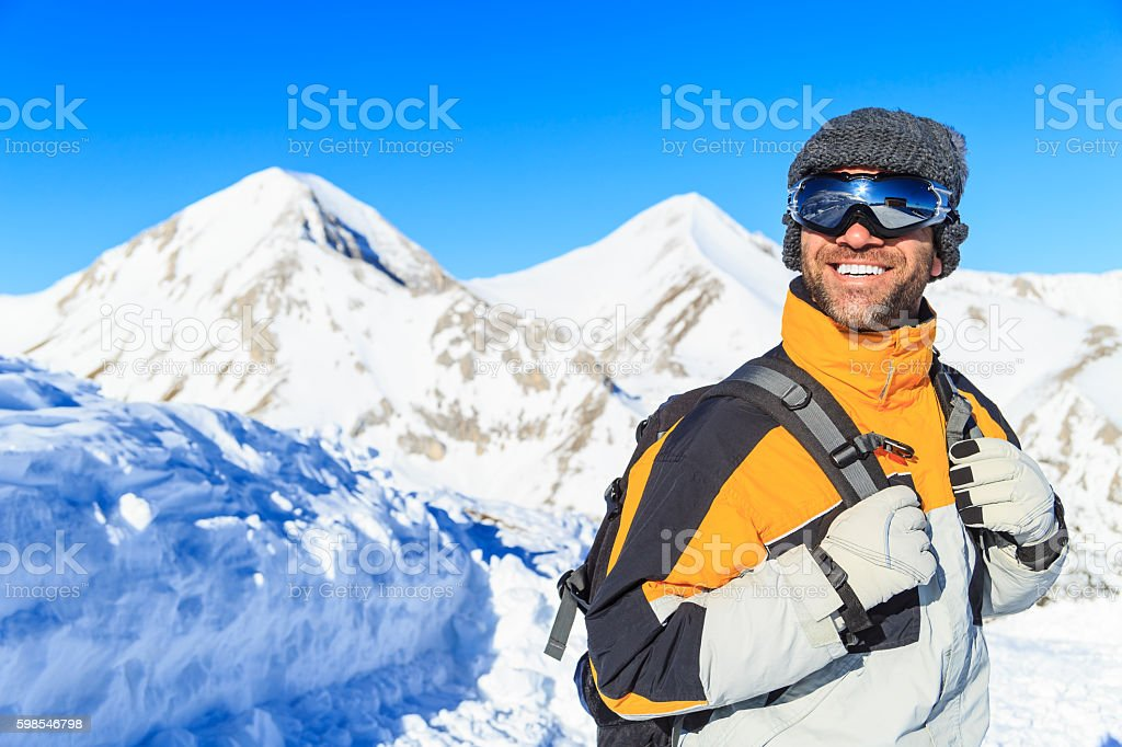 Male backpacker hiking in snow mountain stock photo