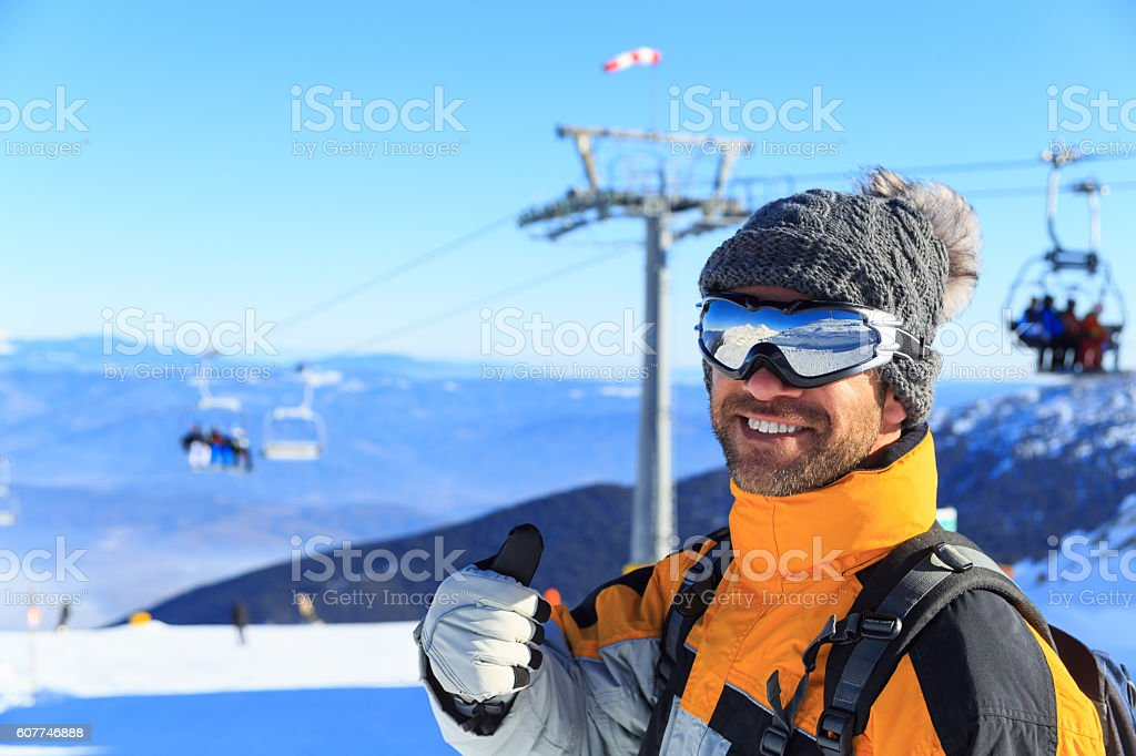 Male backpacker standing in front of a chair lifts stock photo