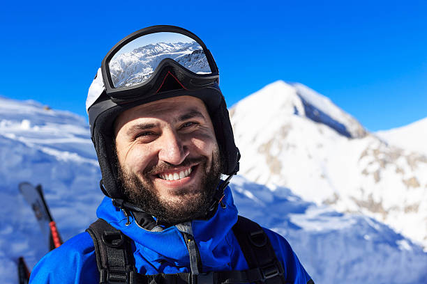 Male backpacker standing on top of the snow mountain stock photo