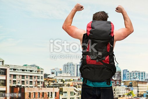 Male backpacker / traveller standing in front of city skyline