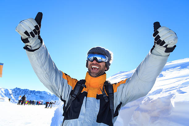 Male backpacker with thumbs up on top snow mountain stock photo