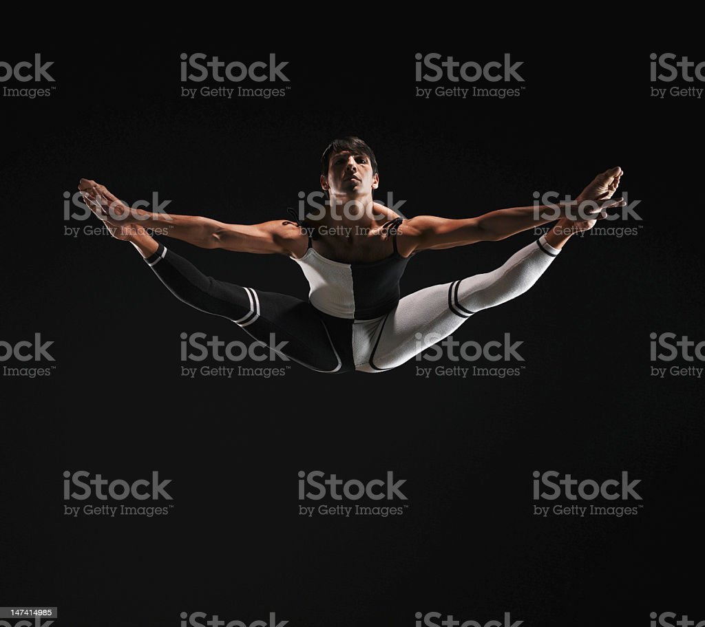 Male ballet dancer in mid air splits, toes pointed royalty-free stock photo