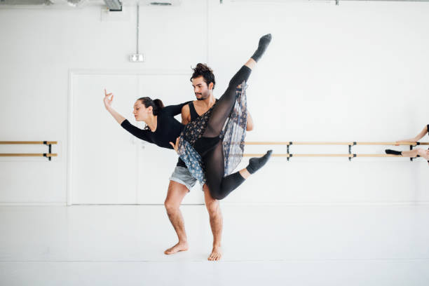 Male ballet dancer picking up female at studio stock photo
