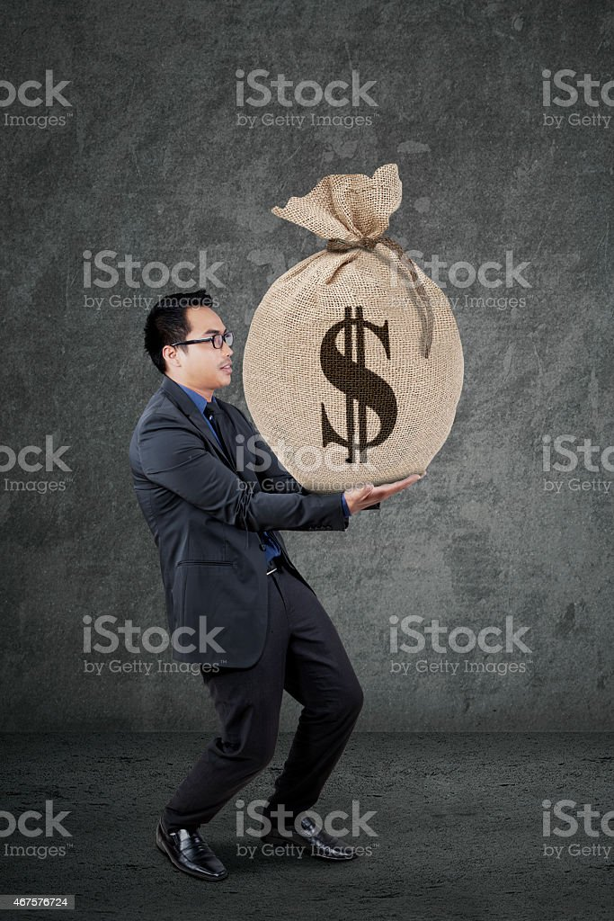 Male banker carrying a money sack stock photo