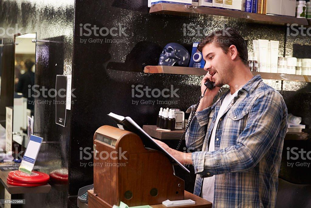 Masculino barbeiro em pé por dinheiro Inscreva-se fazer reserva - foto de acervo