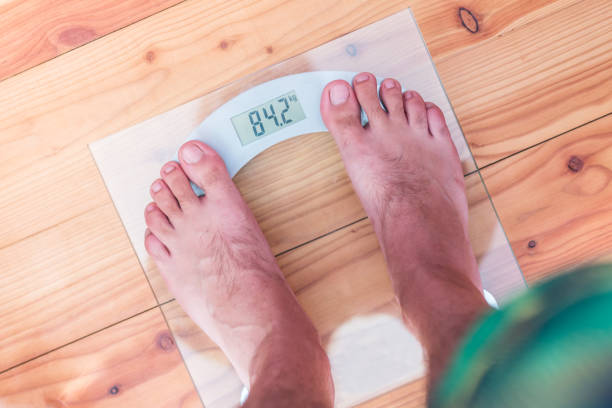 Male bare feet on weight scale stock photo