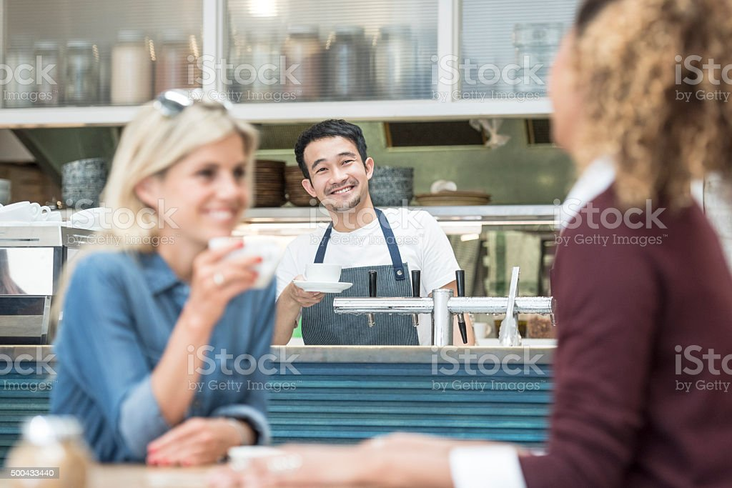 Male barista at counter in cafe with customers in foreground stock photo