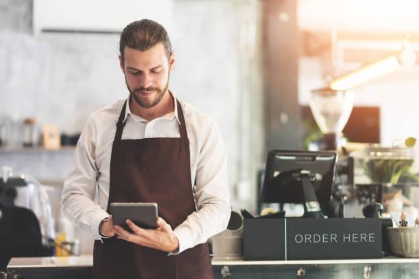 Barista masculino sosteniendo y mirando la tableta digital. - foto de stock