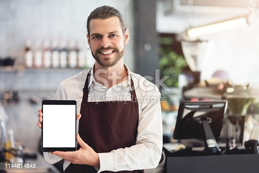 istock Male barista holding and showing a digital tablet. 1144614843