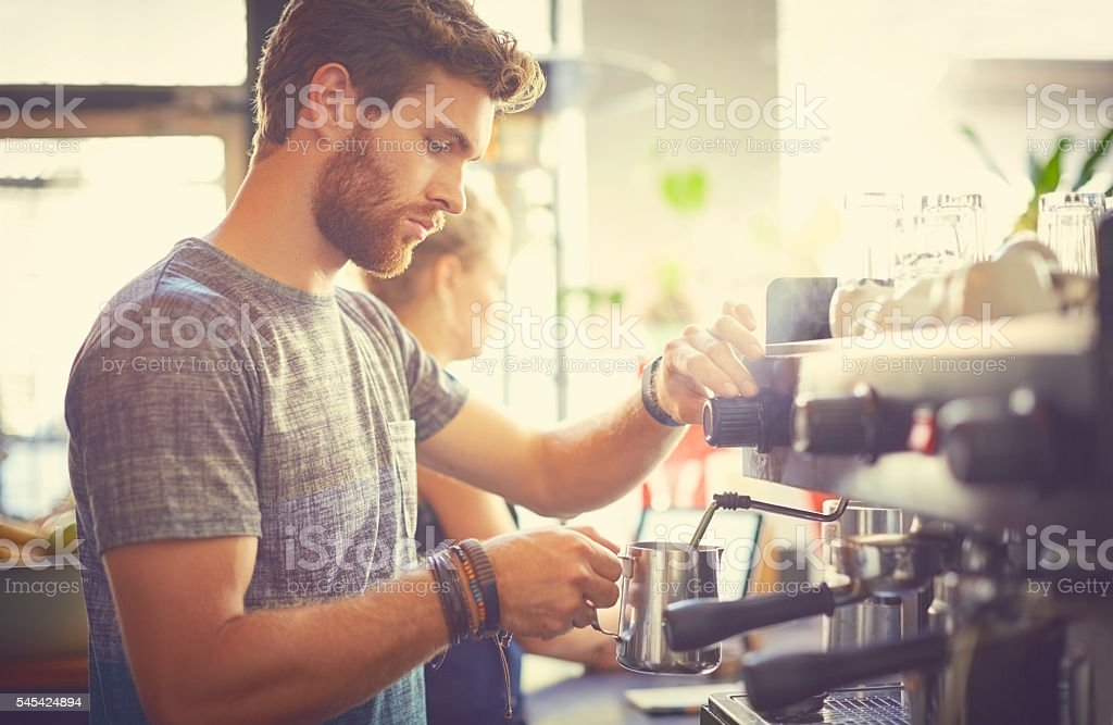 Male barista holding milk jug in cafe stock photo