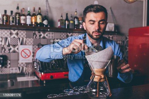 1003493404istockphoto Male barista making filter coffee 1205391174