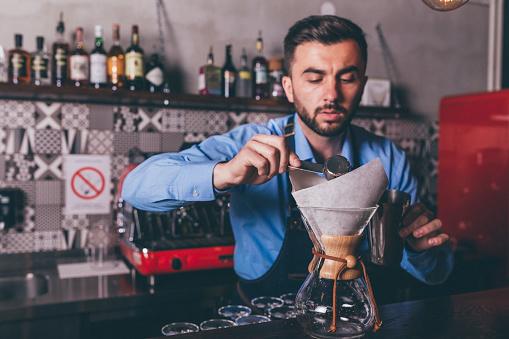 1003493404 istock photo Male barista making filter coffee 1205391174