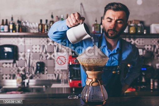 1003493404istockphoto Male barista making filter coffee 1205391267