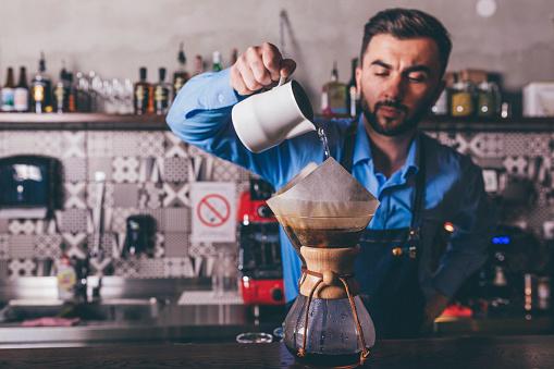 1003493404 istock photo Male barista making filter coffee 1205391267