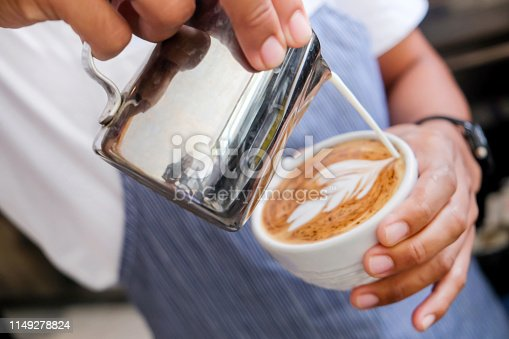 Close up of male barista making a coffee froth art