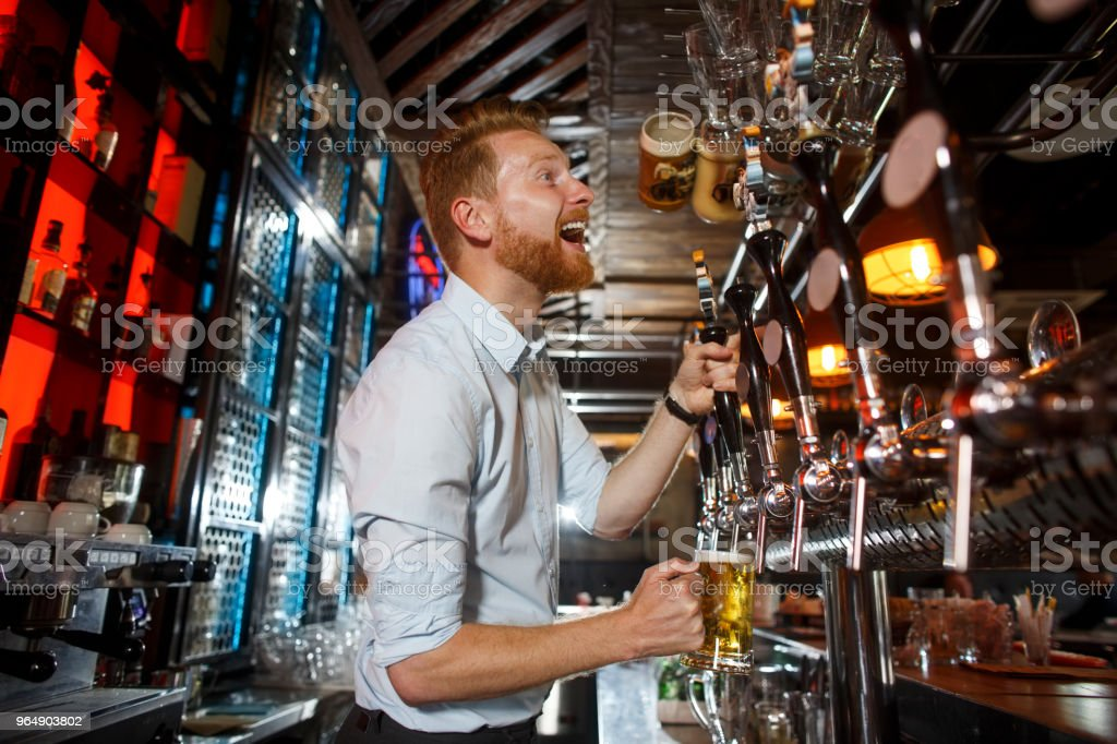 Male barista pouring beer into glass royalty-free stock photo