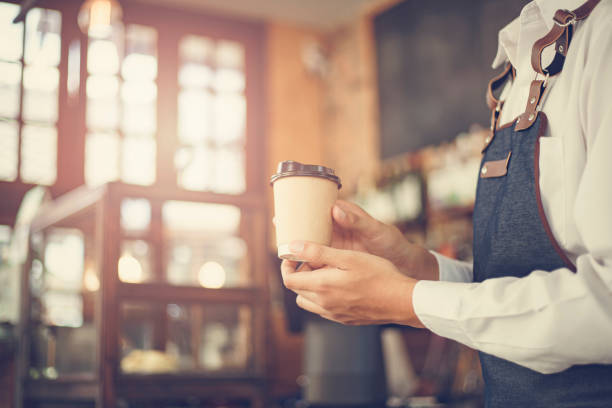 Male Barista preparing coffee for customer in coffee shop. Cafe owner serving a client at the coffee shop. stock photo