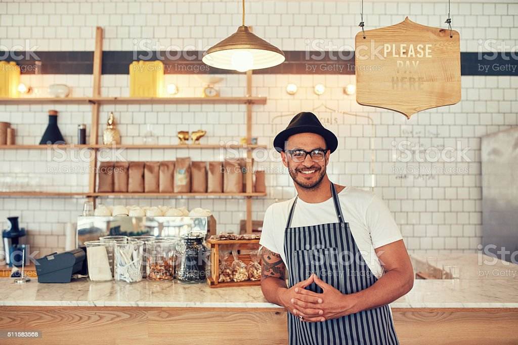 Male barista standing at coffee shop stock photo