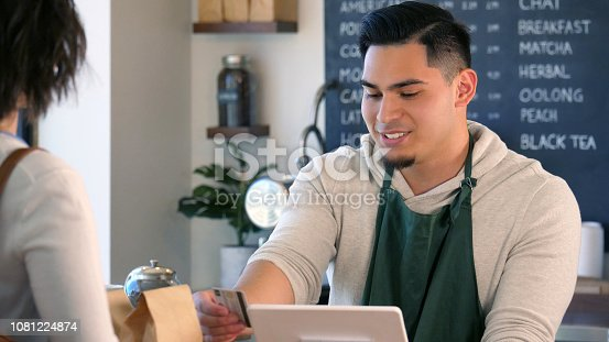 597640822istockphoto Male barista swipes a customer's credit card 1081224874