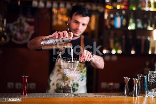 Man bartender pouring alcohol in glass, A young bartender making luxury cocktail.