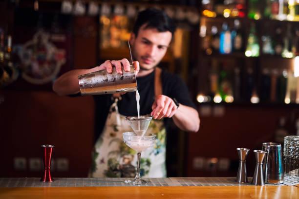 남성 바텐더가 고급 칵테일을 만드는 젊은 바텐더, 유리에 알코올을 붓는. - bartender 뉴스 사진 이미지