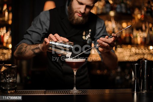 Brutal tattooed male bartender with beard pouring red alcohol cocktail using steel shaker and long bar spoon at bar counter