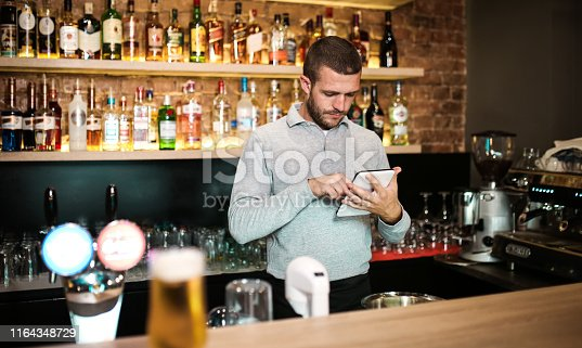 Male bartender working on tablet