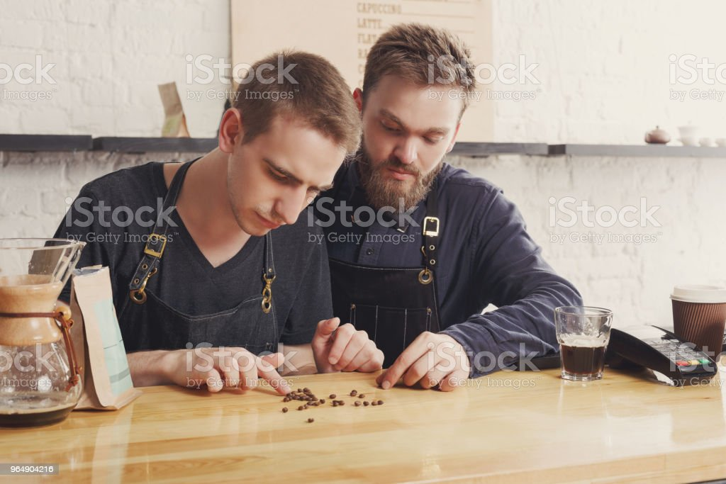Male bartenders brewing fresh coffee at cafe royalty-free stock photo