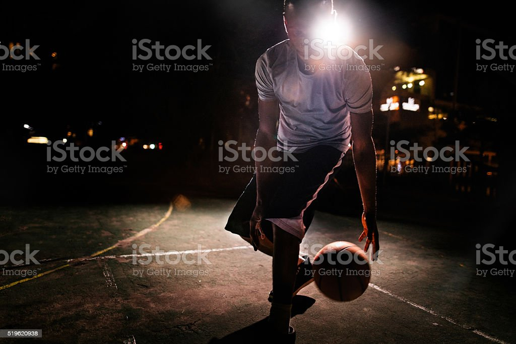 Male Basketball Player Dribbling Ball on Court in Evening stock photo