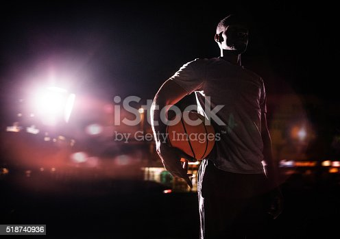 African American urban basketball player holds ball on hip in an inner-city basketball court lit by single street light in background