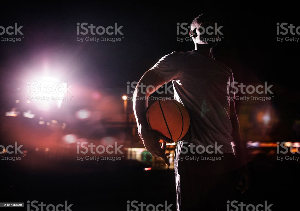 Male basketball Player Holding ball on hip in Evening stock photo