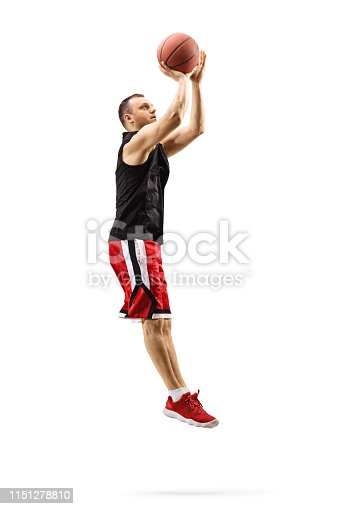 Full length shot of a male basketball player jumping and shooting a ball isolated on white background
