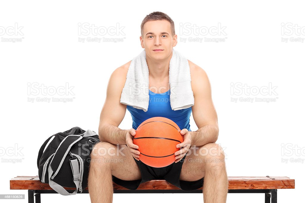 Young male basketball player sitting on a bench isolated on white...