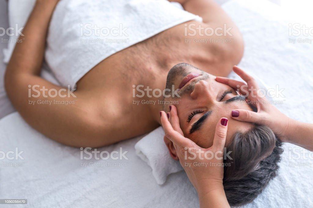 Belleza masculina - hombre recibiendo masaje facial en el spa de lujo - foto de stock