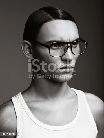 Portrait of handsome young man wearing eyeglasses. Professional make-up and hairstyle. High-end retouch.