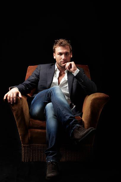 Hombre belleza sentado en un sillón. Imagen de Color - foto de stock