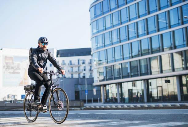 eine männliche fahrradkurier liefern pakete in stadt. kopieren sie raum. - elektrorad stock-fotos und bilder