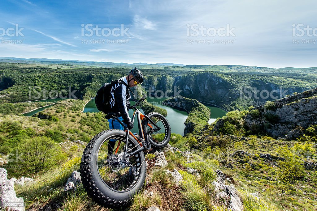 Male bicycle rider standing on top of the hill stock photo