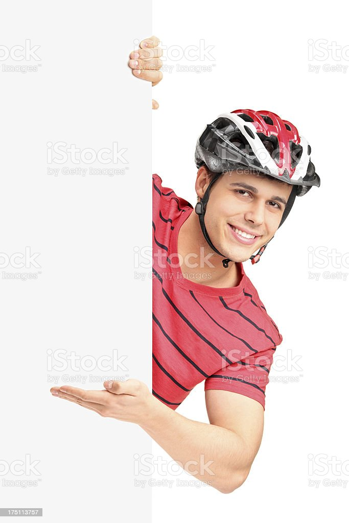 Male bicyclist gesturing behind a panel royalty-free stock photo