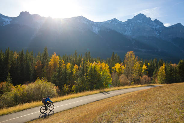 A male bike commuter rides the Trans Canada Trail bike path near Canmore, Alberta, Canada in the fall. He is riding a commuter road bike and is wearing a backpack. Canmore people stock pictures, royalty-free photos & images