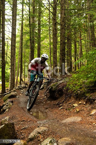 African American man mountain biking in a lush forest. Male biking for recreation. He is living an active lifestyle.