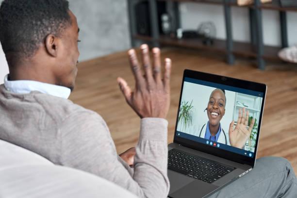 paciente negro macho hablando en videoconferencia a la doctora africana. terapeuta virtual consultando al joven durante la cita en línea en el ordenador portátil en casa. chat de telemedicina, reunión de telesalud - telehealth fotografías e imágenes de stock